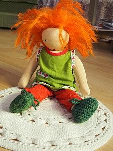 Waldorfpuppe Frieda sitzt auf einem Puppen-Teppich